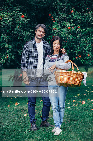 Portrait of couple standing with wicker basket at apple orchard Stock Photo - Premium Royalty-Free, Image code: 698-08007951