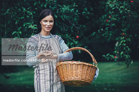 Portrait of woman carrying wicker basket at apple orchard Stock Photo - Premium Royalty-Free, Image code: 698-08007955