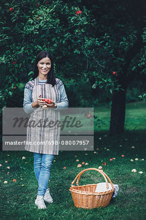 Full length portrait of smiling woman holding fresh apples at orchard Stock Photo - Premium Royalty-Free, Image code: 698-08007957