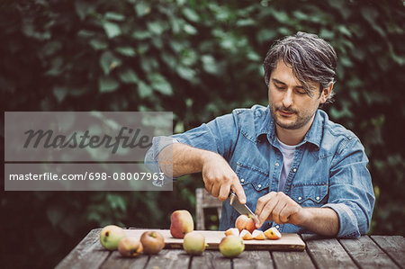 Mid adult man cutting apples at table in organic farm Stock Photo - Premium Royalty-Free, Image code: 698-08007963