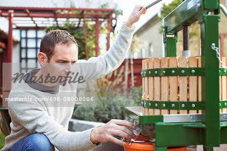 Male farmer collecting fresh apple juice from cider in glass at yard Stock Photo - Premium Royalty-Free, Image code: 698-08008006
