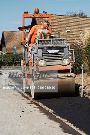 Construction worker driving road roller on street Stock Photo - Premium Royalty-Free, Image code: 698-08008010
