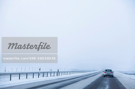 Car on E4 highway during winter against clear sky Stock Photo - Premium Royalty-Free, Image code: 698-08008038