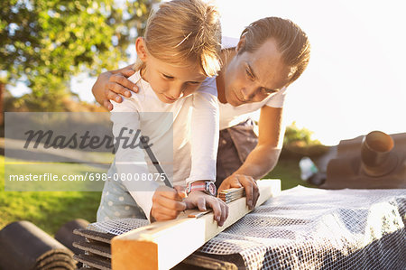 Father assisting daughter in measuring plank Stock Photo - Premium Royalty-Free, Image code: 698-08008075