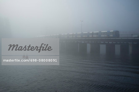 Train passing on railway bridge over sea in foggy weather Stock Photo - Premium Royalty-Free, Image code: 698-08008091