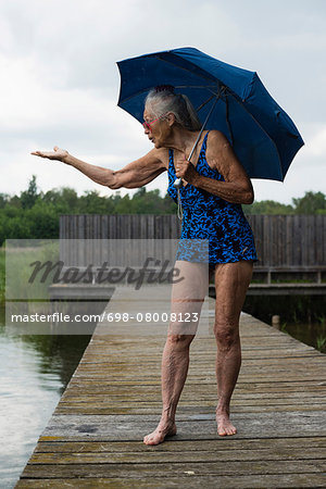 Senior woman in swimwear with umbrella gesturing while standing boardwalk at lake Stock Photo - Premium Royalty-Free, Image code: 698-08008123