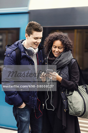 Multi-ethnic couple listening music through mobile phone on subway platform Stock Photo - Premium Royalty-Free, Image code: 698-08008137