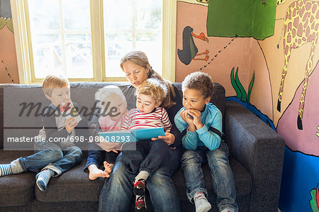 Teacher telling story to children in kindergarten Stock Photo - Premium Royalty-Free, Image code: 698-08008293