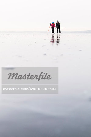 Father and daughter ice-skating on frozen lake Stock Photo - Premium Royalty-Free, Image code: 698-08008303