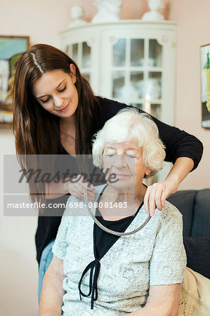 Granddaughter putting on necklace to grandmother at home Stock Photo - Premium Royalty-Free, Image code: 698-08081483