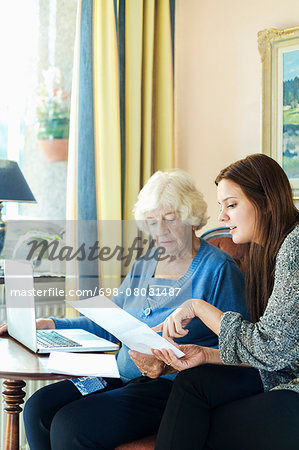 Grandmother and granddaughter reading document while using laptop at home Stock Photo - Premium Royalty-Free, Image code: 698-08081487