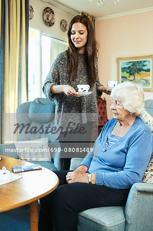 Young woman holding coffee cups while standing by grandmother at home Stock Photo - Premium Royalty-Free, Image code: 698-08081489