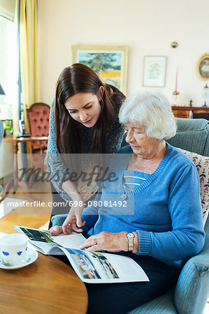Grandmother and granddaughter reading magazine together in living room Stock Photo - Premium Royalty-Free, Image code: 698-08081492