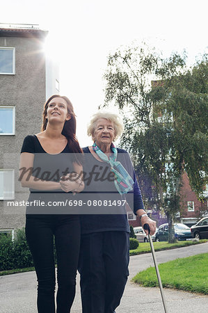Granddaughter assisting grandmother to walk on footpath Stock Photo - Premium Royalty-Free, Image code: 698-08081497