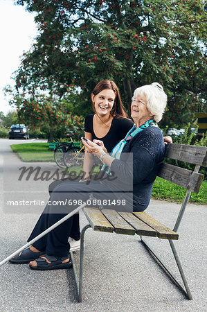Happy grandmother and granddaughter using mobile phone on park bench Stock Photo - Premium Royalty-Free, Image code: 698-08081498