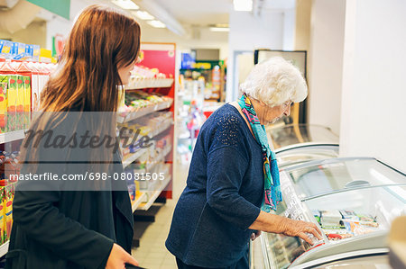 Young woman looking at grandmother shopping in supermarket Stock Photo - Premium Royalty-Free, Image code: 698-08081505