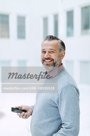 Portrait of happy businessman listening music through smart phone in office Stock Photo - Premium Royalty-Free, Image code: 698-08081518