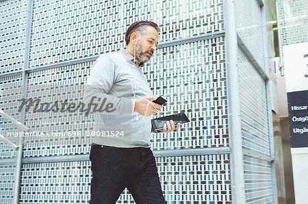 Businessman with digital tablet listening music though mobile phone while walking in office Stock Photo - Premium Royalty-Free, Image code: 698-08081524