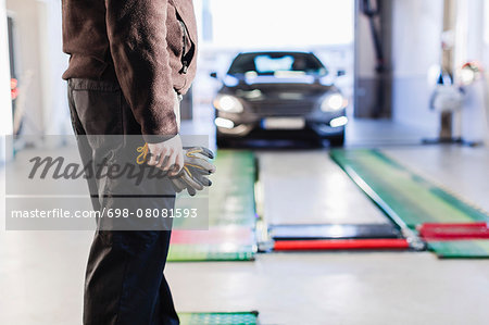 Midsection of mechanic standing in front of car coming towards hydraulic lift Stock Photo - Premium Royalty-Free, Image code: 698-08081593