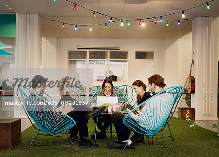 Creative business people using technologies in office canteen Stock Photo - Premium Royalty-Free, Image code: 698-08081637