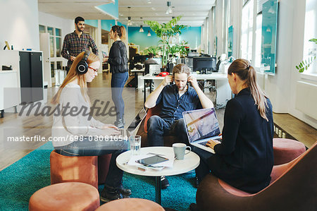 Business people using laptops in creative office Stock Photo - Premium Royalty-Free, Image code: 698-08081654
