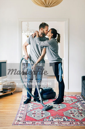 Full length of man kissing woman while vacuuming carpet at home Stock Photo - Premium Royalty-Free, Image code: 698-08081780