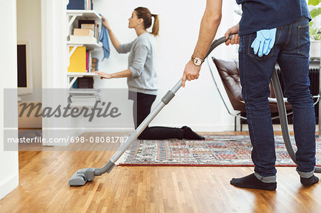 Low section of man vacuuming floor while woman cleaning shelves in background at home Stock Photo - Premium Royalty-Free, Image code: 698-08081787
