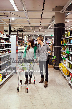 Young couple walking while shopping in supermarket Stock Photo - Premium Royalty-Free, Image code: 698-08081803