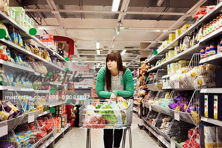 Young woman leaning on shopping cart at supermarket aisle Stock Photo - Premium Royalty-Free, Image code: 698-08081807