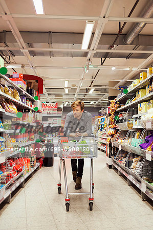 Young man leaning on shopping cart at supermarket aisle Stock Photo - Premium Royalty-Free, Image code: 698-08081809