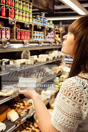 Woman shopping cheese in supermarket Stock Photo - Premium Royalty-Free, Image code: 698-08081811