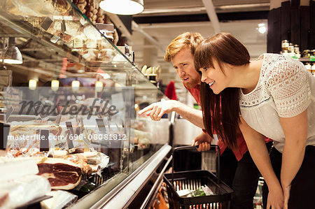 Young couple choosing fresh meat at supermarket Stock Photo - Premium Royalty-Free, Image code: 698-08081812