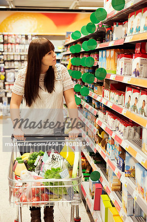 Woman looking at products while shopping in supermarket Stock Photo - Premium Royalty-Free, Image code: 698-08081814