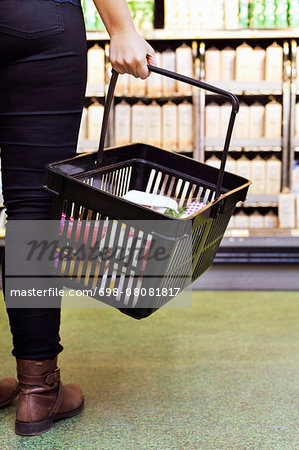 Low section of woman carrying basket in supermarket Stock Photo - Premium Royalty-Free, Image code: 698-08081817