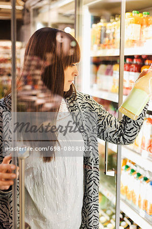 Young woman reading label on juice at refrigerated section in supermarket Stock Photo - Premium Royalty-Free, Image code: 698-08081822