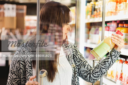 Young woman reading label on juice bottle at refrigerated section in supermarket Stock Photo - Premium Royalty-Free, Image code: 698-08081823
