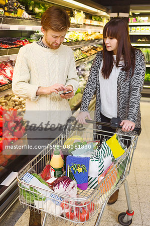 Young couple using mobile phone while buying groceries at supermarket Stock Photo - Premium Royalty-Free, Image code: 698-08081830