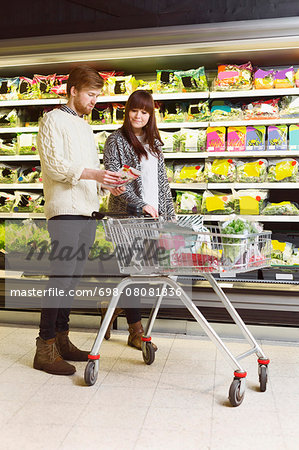 Young couple analyzing product in supermarket Stock Photo - Premium Royalty-Free, Image code: 698-08081836