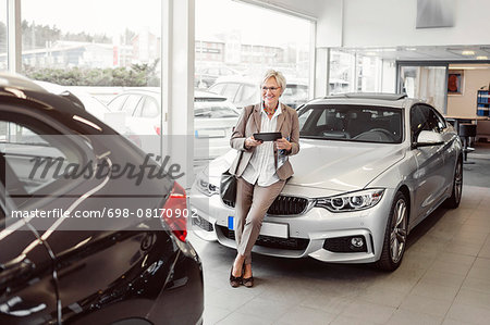 Happy businesswoman with digital tablet looking at car in store Stock Photo - Premium Royalty-Free, Image code: 698-08170902