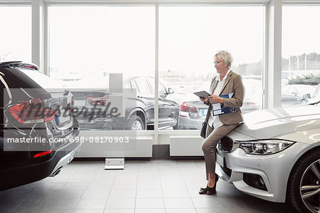 Full length of businesswoman with digital tablet sitting on car at store Stock Photo - Premium Royalty-Free, Image code: 698-08170903