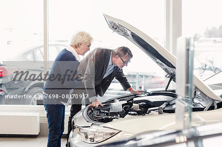 Senior couple examining car engine in showroom Stock Photo - Premium Royalty-Free, Image code: 698-08170917