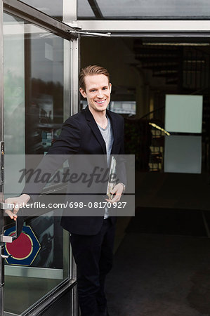 Portrait of happy salesman standing at entrance of car showroom Stock Photo - Premium Royalty-Free, Image code: 698-08170927