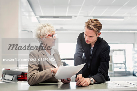 Two sales colleagues discussing documents at car dealership Stock Photo - Premium Royalty-Free, Image code: 698-08170932