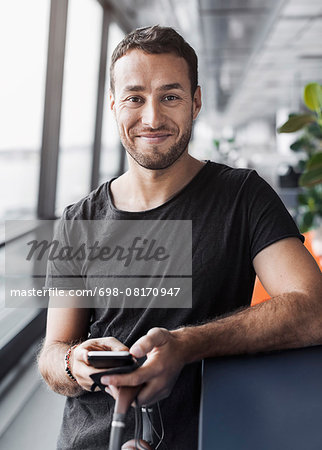 Portrait of smiling businessman holding mobile phone while leaning on cubicle in office Stock Photo - Premium Royalty-Free, Image code: 698-08170947