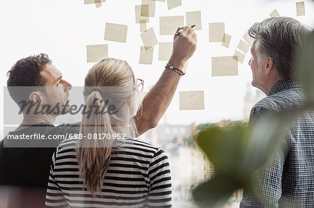 Businessman explaining adhesive notes to colleagues in office Stock Photo - Premium Royalty-Free, Image code: 698-08170952