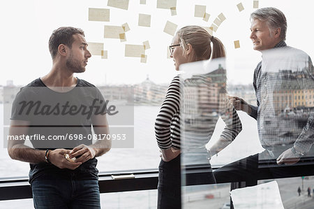 Business colleagues discussing by glass window in office Stock Photo - Premium Royalty-Free, Image code: 698-08170953