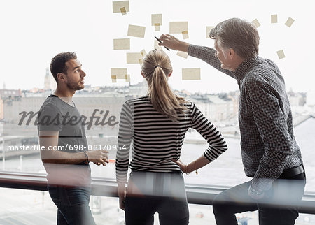 Businessman explaining adhesive notes to colleagues in office Stock Photo - Premium Royalty-Free, Image code: 698-08170954