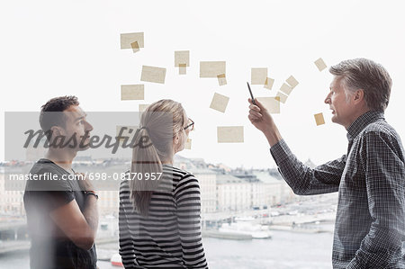 Business people discussing over adhesive notes stuck to glass window Stock Photo - Premium Royalty-Free, Image code: 698-08170957