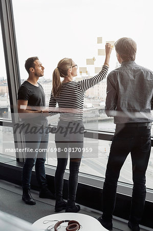 Business colleagues discussing over adhesive notes stuck to glass window Stock Photo - Premium Royalty-Free, Image code: 698-08170959