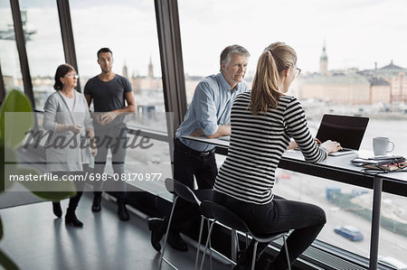 Business people discussing by window in office Stock Photo - Premium Royalty-Free, Image code: 698-08170977